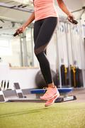 Healthy young woman skipping rope in a gym, crop Stock Photos