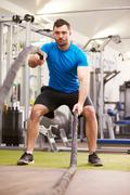Young man working out with battle ropes at a gym, vertical Stock Photos
