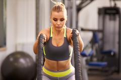 Young woman preparing to work out with battle ropes at a gym Stock Photos