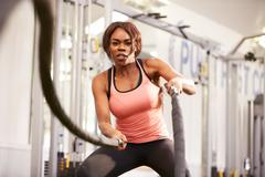 Young woman working out with battle ropes at a gym Stock Photos