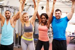 Happy, healthy group of people with arms in the air at a gym Stock Photos