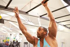 Muscular man working out on monkey bars at a gym Stock Photos