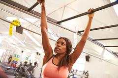 Young woman hanging from monkey bars at a gym Stock Photos