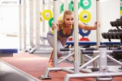 Woman working out using equipment at a gym Stock Photos