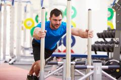 Young man working out using equipment at a gym Stock Photos
