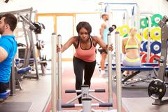 Young woman working out using equipment at a gym Stock Photos