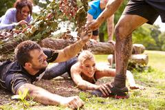 Assault course competitor helping others crawl under nets Stock Photos
