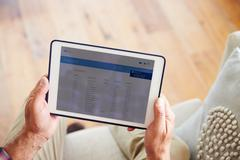 Man Looking At Banking App On Digital Tablet - stock photo