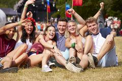 Friends sitting on the grass cheering at a music festival Stock Photos