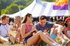 Friends sitting on grass using smartphone at music festival - stock photo