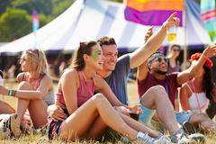 Friends sitting on grass having fun at a music festival Stock Photos