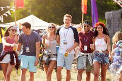 Group of friends walking through a music festival site - stock photo