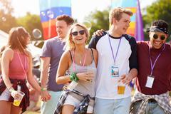 Friends friends walking through a music festival site Stock Photos