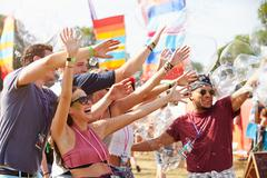 Friends enjoying a performance at a music festival Stock Photos