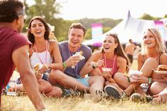 Friends sitting on grass and eating at music festival Stock Photos