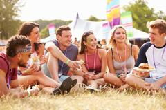Friends sitting on grass and eating at music festival - stock photo