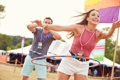 Woman with hula hoop at a music festival, man in background Stock Photos