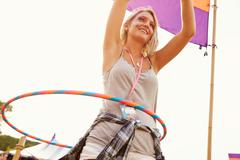 Blonde woman dancing with hula hoop at a music festival Stock Photos