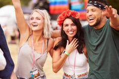 Three friends in the audience at a music festival - stock photo