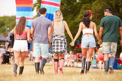 Friends walking together at a music festival site, back view Stock Photos