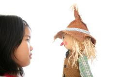 Asian girl looking her scarecrow toy - stock photo