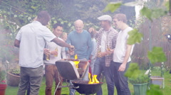 4K Happy mixed ethnicity group of male friends chatting & drinking beer at bbq - stock footage
