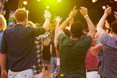 Back view of audience at a music festival - stock photo