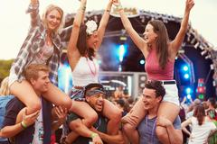 Friends having fun in the crowd at a music festival Stock Photos