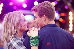 Couple looking at each other in the crowd at music festival Stock Photos