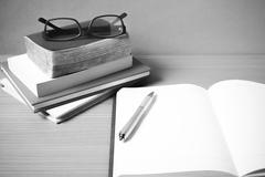 open notebook with stack of book black and white color tone style - stock photo