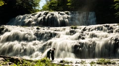 Timelapse of people playing on a beautiful jungle waterfall Stock Footage