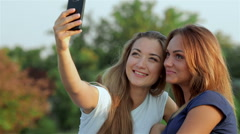Two girlfriends make Selfies on mobile phone - stock footage
