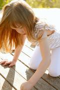 Little girl playing on park wooden floor - stock photo