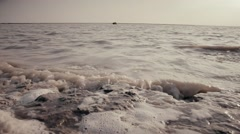 Stock Video Footage of  waves whipped foam on the horizon silhouette of a boat with people