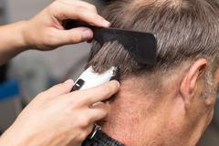 Close up of a male student having a haircut with hair clippers - stock photo