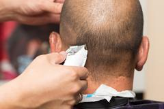 Close up of a male student having a haircut with hair clippers Stock Photos