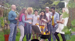 4K Happy mixed ethnicity group of friends chatting & drinking beer at bbq Stock Footage