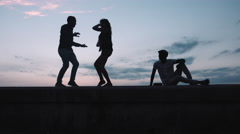 Friends dancing on retaining wall Stock Footage