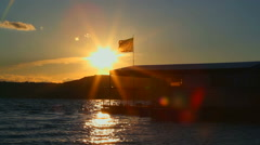 Boat with a flag on sunset Stock Footage