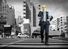 Stock Photo of Architect in protective helmet speaking by phone on the crossroad