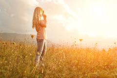 Stock Photo of Happiness woman stay outdoor under sunlight of sunset