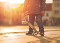 Stock Photo of Child with skateboard on the street at sunset light.