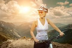 Beautiful woman in helmet and glasses stay on the bicycle around - stock photo