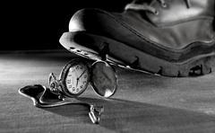 Old boot treading a vintage pocket watch Kuvituskuvat