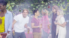 4K Happy mixed ethnicity group of friends chatting & drinking beer at bbq - stock footage