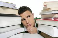 Young unhappy student with stacked books Stock Photos