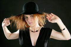 beautiful redhead woman in black, hat and jewels - stock photo