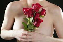 Romantic nude woman holding red roses Stock Photos