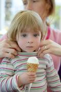 Beautiful toddler eating ice cream, mother care - stock photo