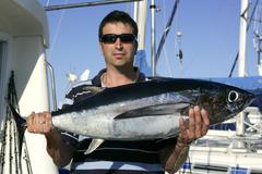 Big game fisherman with saltwater tuna - stock photo